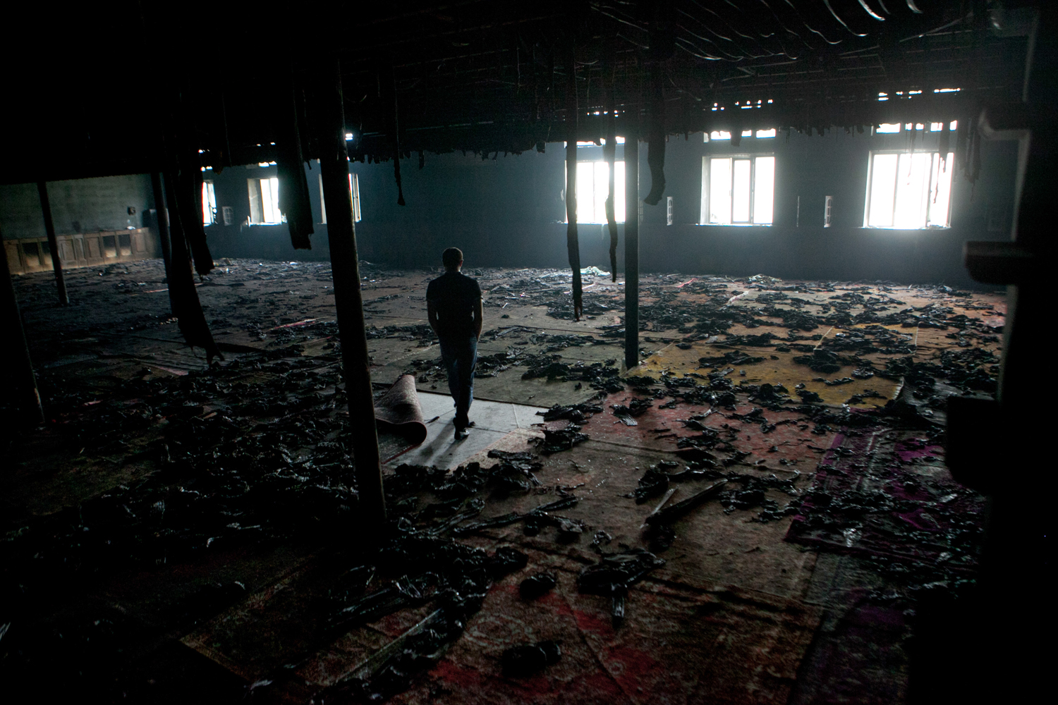 A man seen in a burned mosque. Three days prior, unknown armed personnel came here after the evening prayer, killed the imam and two parishioners and burned the mosque.