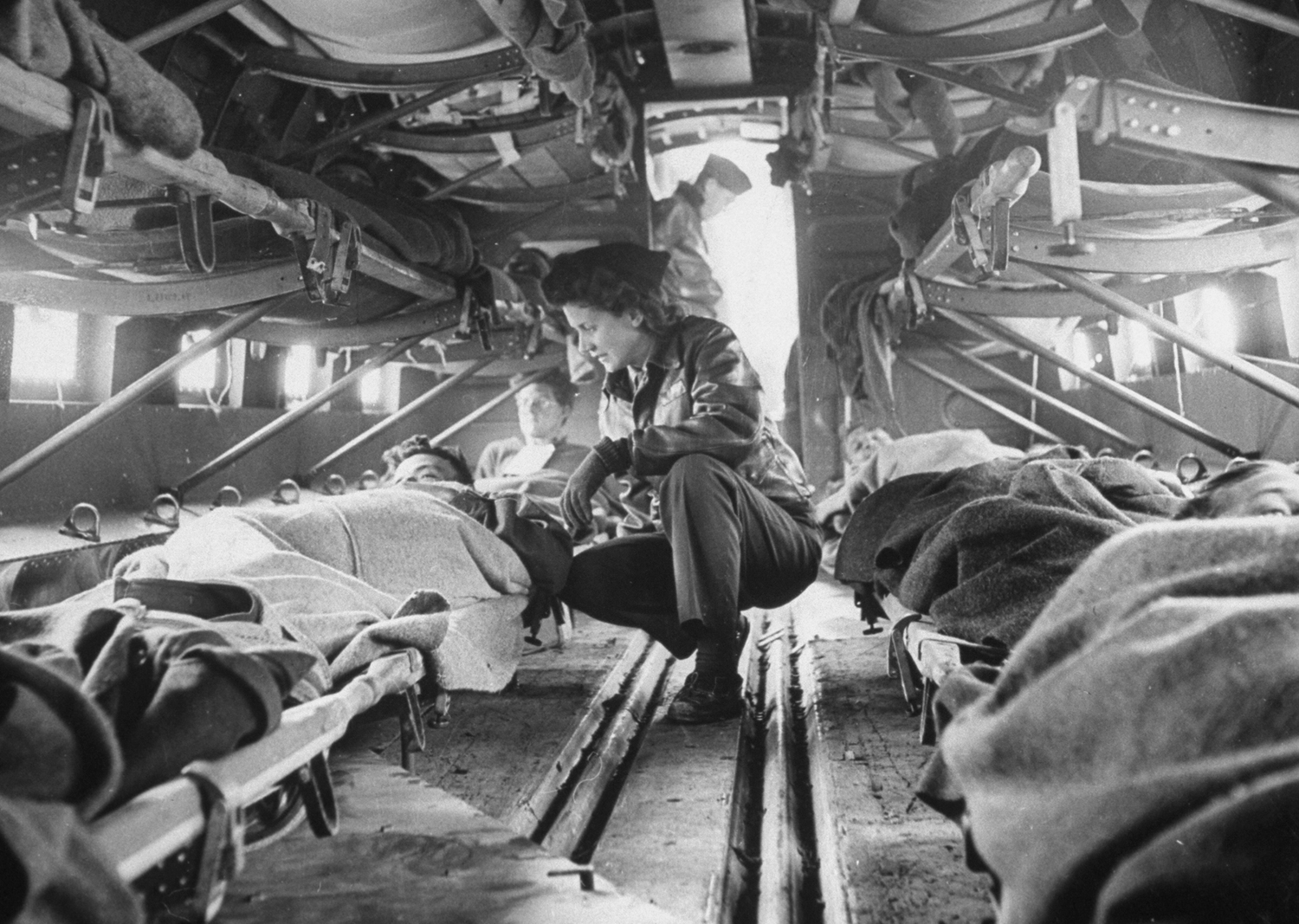 Somewhere over North Africa an American  flying nurse,  Second Lieut. Julia Corinne Riley, 23, checks on patients aboard a specially outfitted C-47 transport plane, used to ferry wounded men to hospitals, spring 1943.
