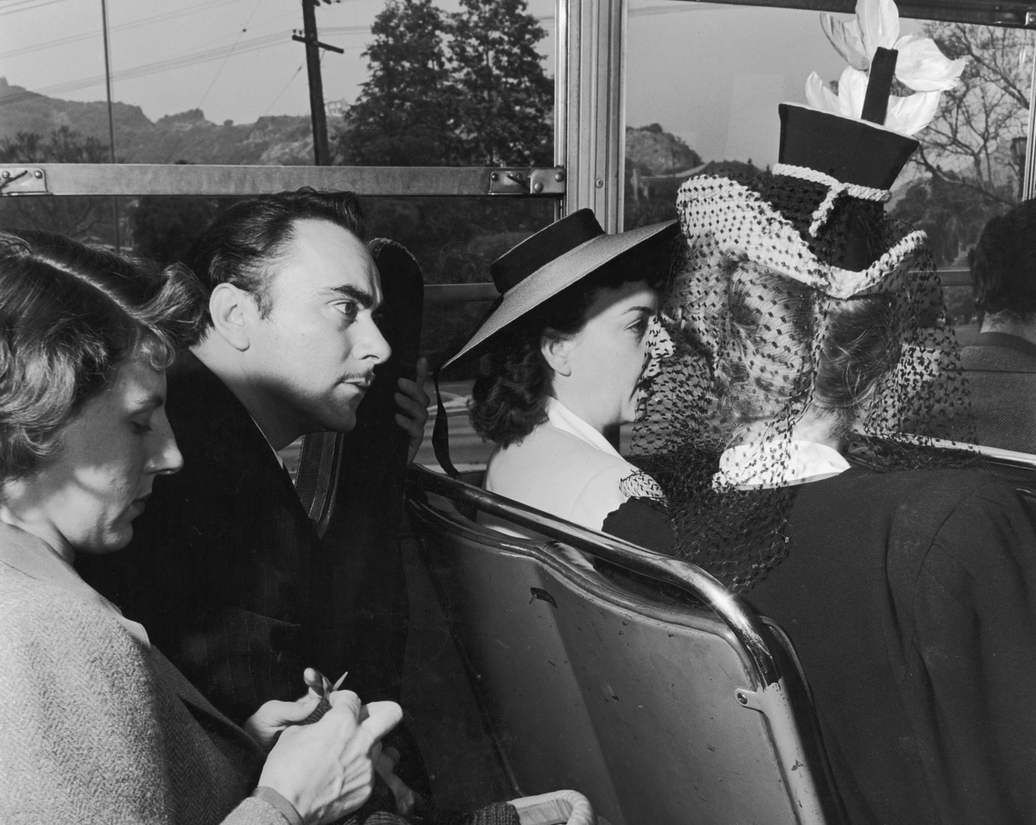 "<strong>Caption from LIFE.</strong> ""Busing home from Sunday services, the blonde girl in the funny hat tells her friend: 'I'm sure now, those Zenith soldiers are sailing from Alaska. He didn't ask us to pray last Sunday, so they must be leaving this week.' In bus seat behind them, a musician leans forward to overhear their conversation."""