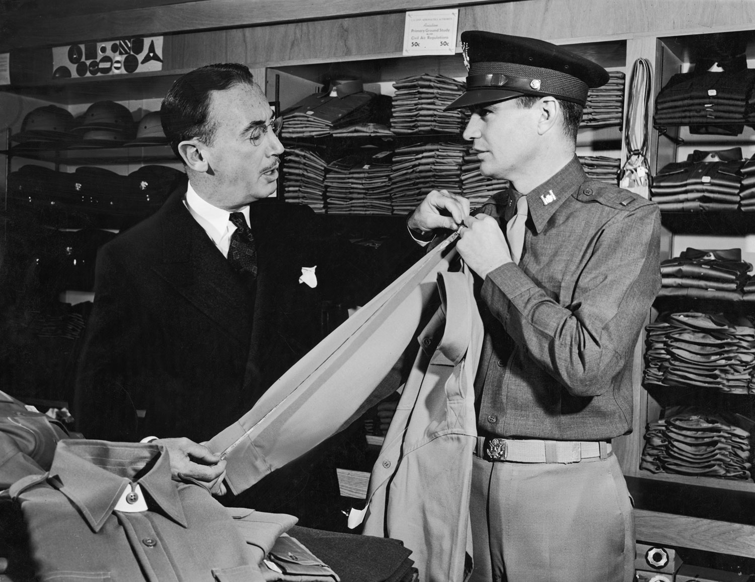 "<strong>Caption from LIFE.</strong> ""A dozen tropical shirts are ordered by a young Army lieutenant in the store of the Zenith haberdasher the next evening just before closing time. But the sleeves are too long and will have to be altered. The lieutenant says: 'If you can't get them done and delivered to my hotel by 9 o'clock Friday night, never mind the order. I won't be able to pay for them if I've gone when they're delivered. Understand?' The haberdasher says he understands. But he muses to himself: 'Tropical shirts. This young fellow must be headed to Australia.'"""