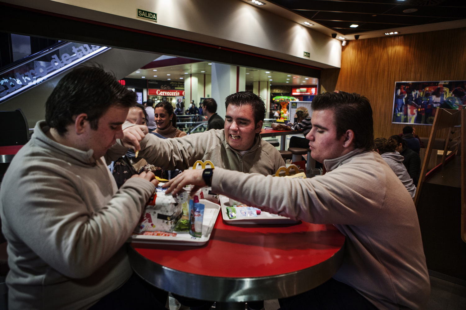 Álvaro shields himself from his brothers after taking away a french fry in a restaurant in Seville.