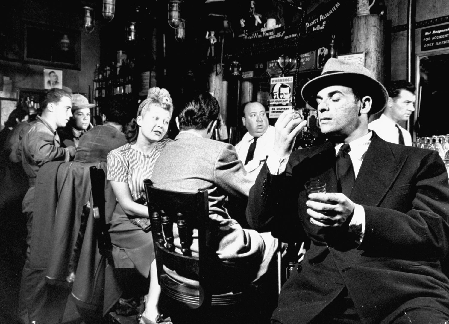 "<strong>Caption from LIFE.</strong> ""At the Friendship Cafe the manicurist tells her boyfriend: 'A customer told me today that lots of our troopships are sailing to Australia on Friday at midnight.' The shady-looking man standing next to them listens attentively. (Note bartender played by Alfred Hitchcock, center)."""