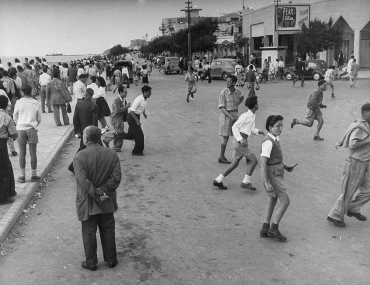 People run away from the waterfront during an air raid shortly after the establishment of the state of Israel, exact location unknown, May 1948.