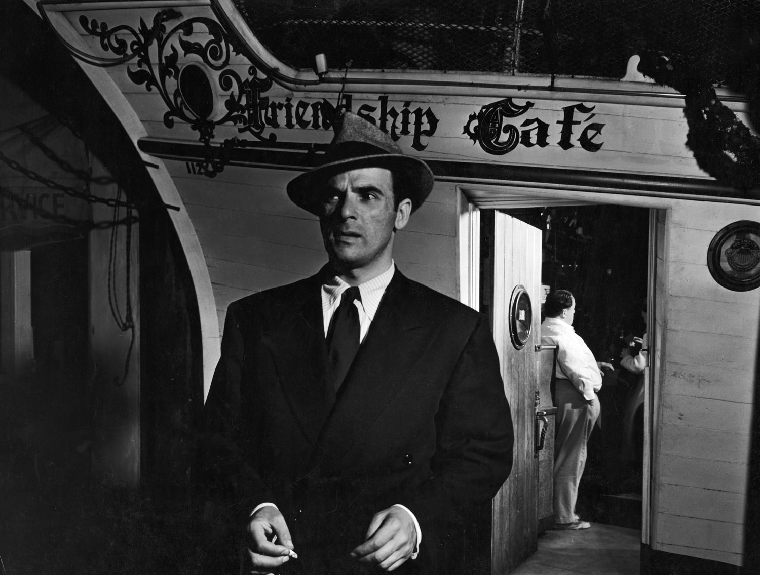 "<strong>Caption from LIFE.</strong> ""The mysterious man, whose ears were even more attentive than the manicurist's boyfriend, leaves the cafe, remembering these important words: 'Troopships ... Australia ... Friday at midnight.' His business is to check all rumors, not pass them along for social conversation."""