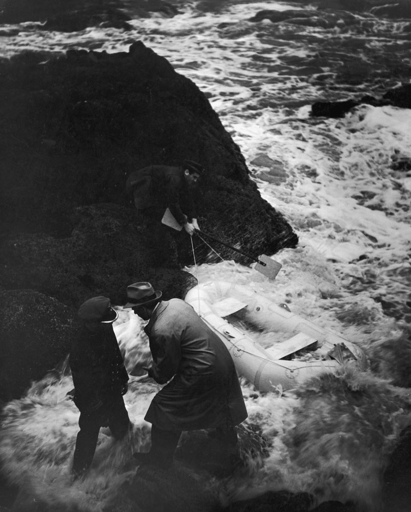 "<strong>Caption from LIFE.</strong> ""A midnight rendezvous is held by a mysterious man, an Axis agent, with a U-boat officer and seaman who have paddled ashore in a small rubber boat. In the dark cove, the secret military information the haberdasher so innocently revealed to his family at last reaches the enemy."""