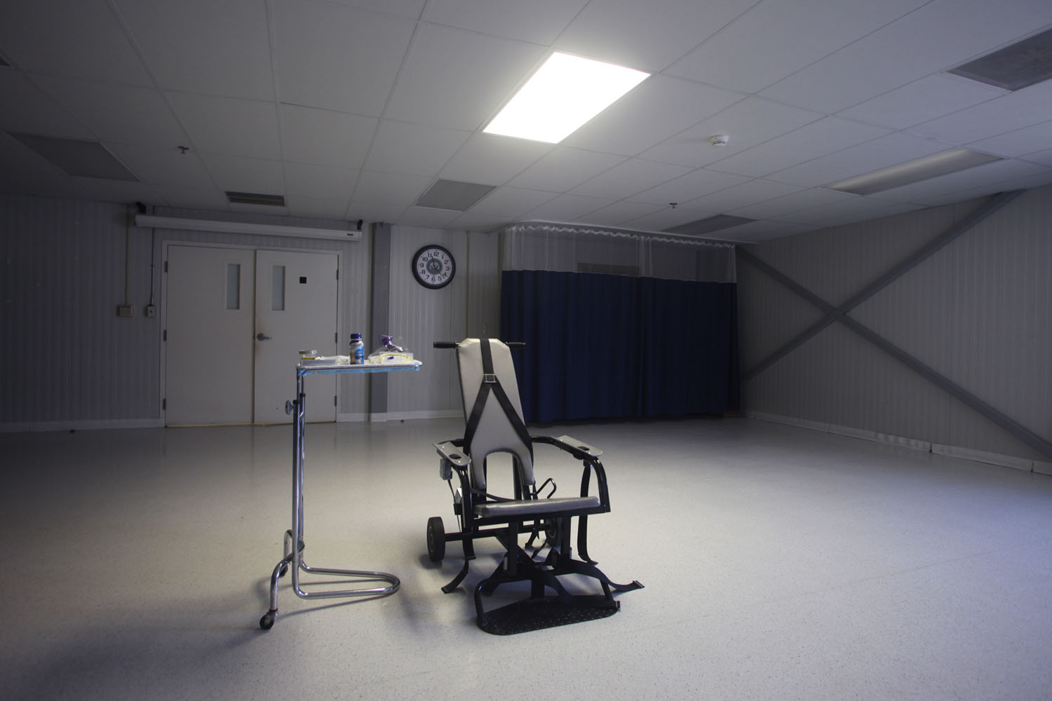 A restraining chair and force-feeding apparatus on display in an empty room of the detainee hospital.