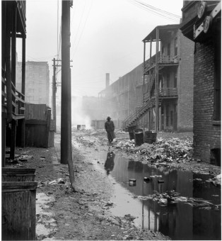 An alley between overcrowded tenements, with garbage thrown over the railings of the back porches. Most of the area's tenants were transient. Chicago, 1948.