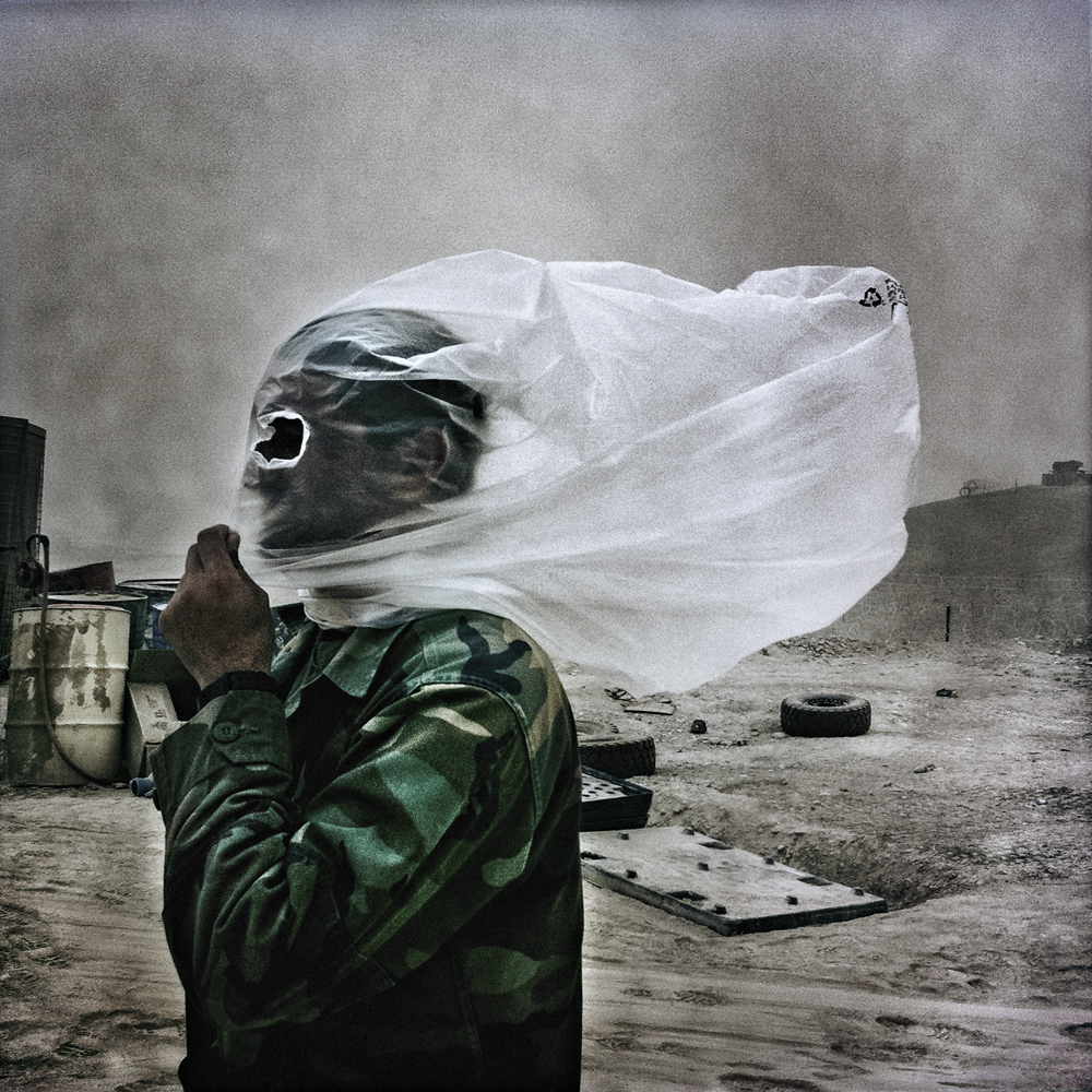 An Afghan National Army soldier protects his face from a sudden dust storm at Combat Outpost 7171 in Helmand Province, Afghanistan on October 28, 2010.