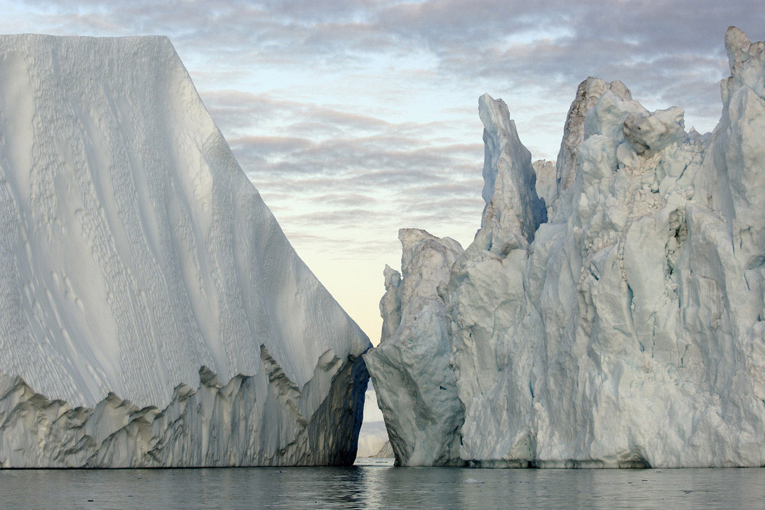 In Disko Bay, Greenland, 20-story high icebergs broken off from the Greenland Ice Sheet float into the North Atlantic, raising sea level.