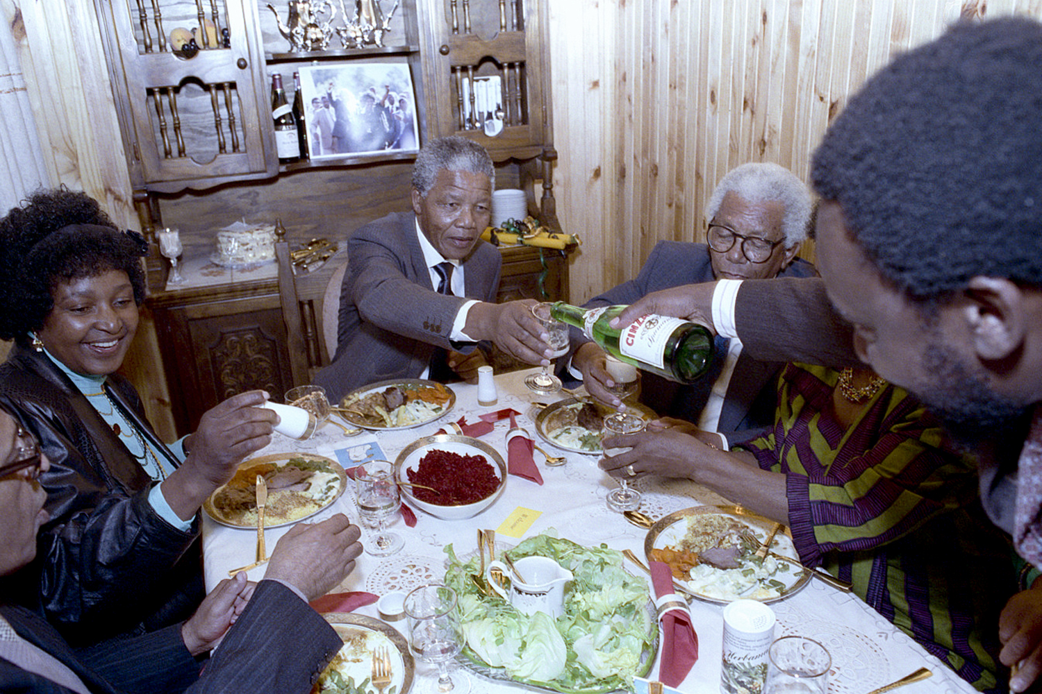 Nelson Mandela shares his first meal at the Mandela home in Soweto with his family and fellow inmate of 27 years, Walter Sisulu. The man pouring champagne, Cyril Ramaphosa, who many believe could be the next President of South Africa.