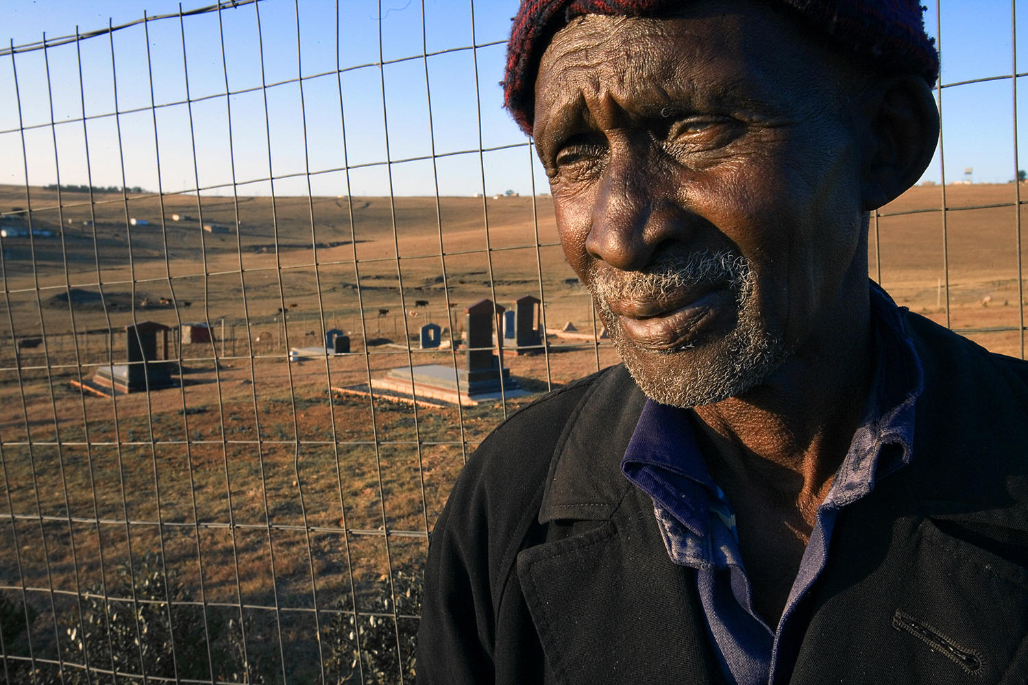 On a hillside outside of Qunu in the Transkei, a man who referred to himself as one of Mandela's brothers, stands in front of the family cemetery where it is commonly thought Mandela will be buried. 2007.