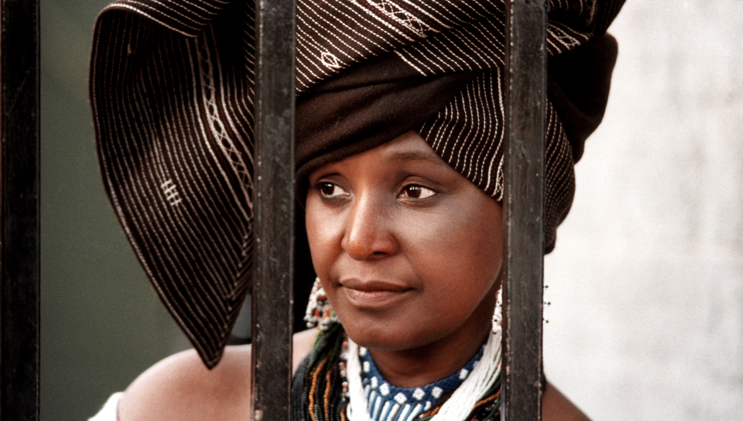Winnie Mandela fell in love with and married Nelson Mandela when she was 24 years old. They had two children — both girls— during the two years before Mandela went to prison. Winnie herself was placed in solitary confinement for 18 months and was banished for nine years under house arrest in Brandfort. Through it all, Winnie remained the public persona of her husband. 1986.