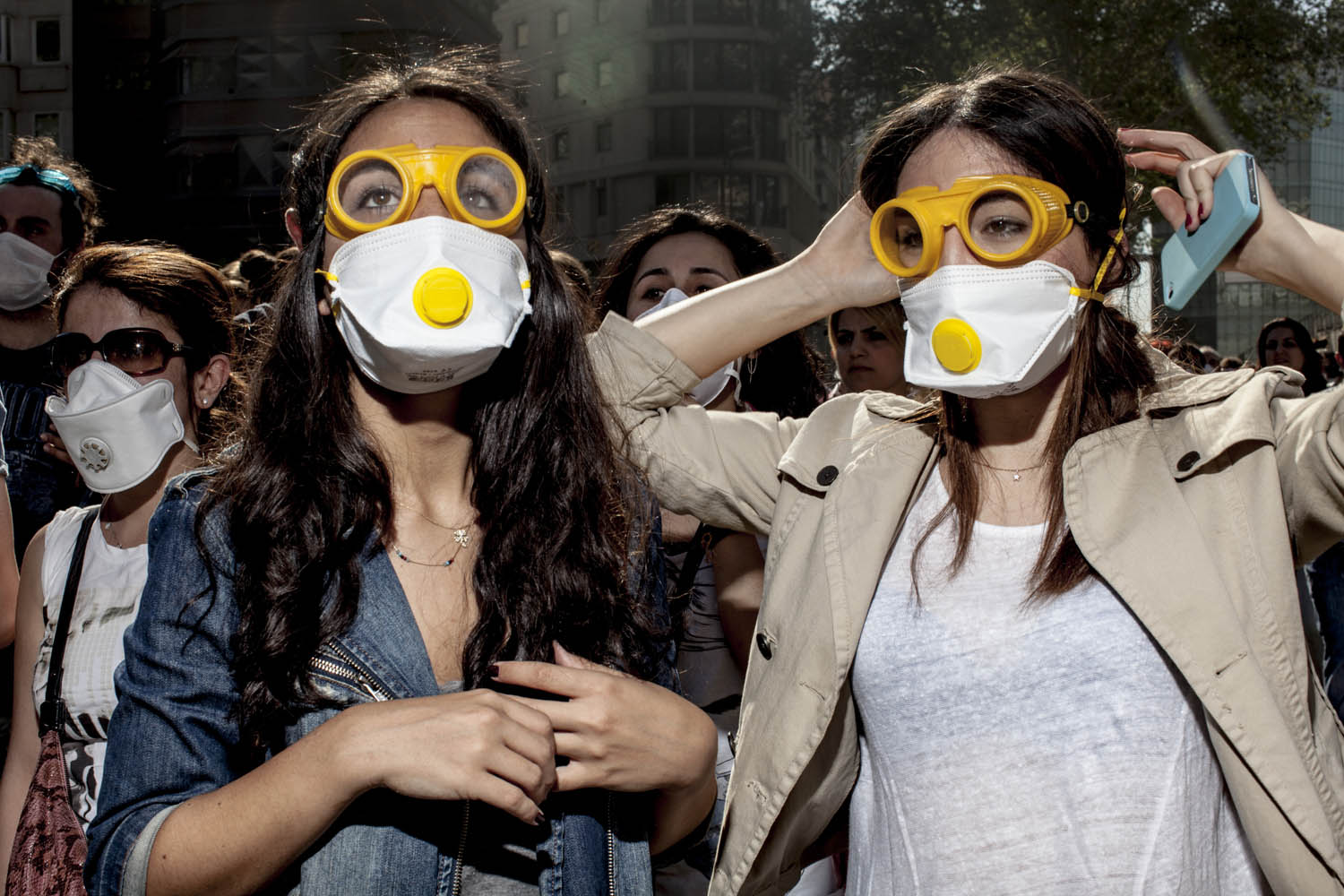 June 1, 2013. Young women watch rounds of tear gas canisters as they travel in their direction in Istanbul, Turkey.
