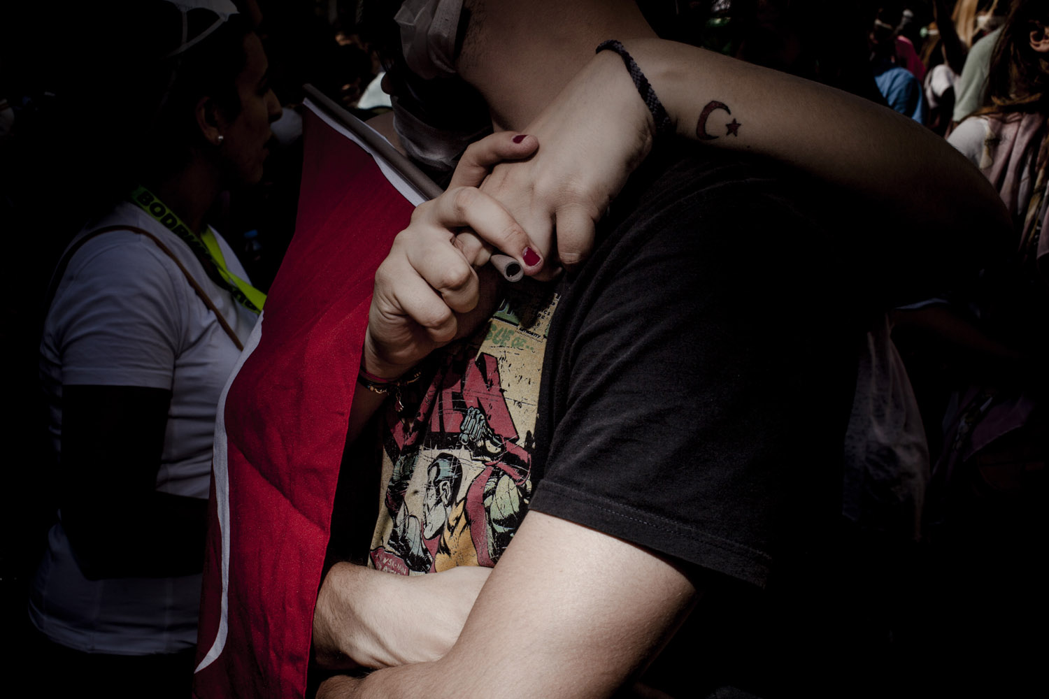 A young couple embraces at the entrance to Gezi Park after riot police fired a volley of tear gas.