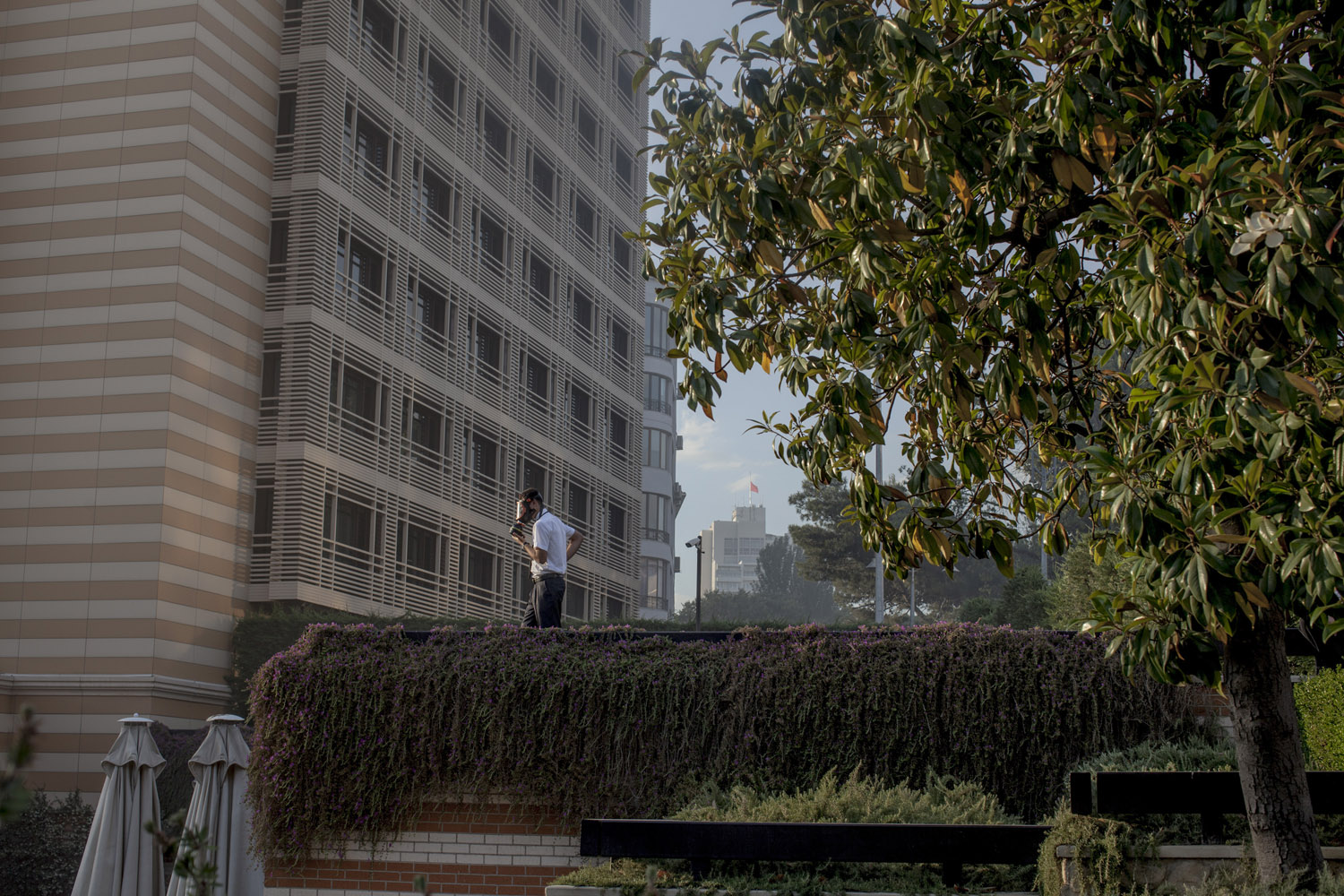 A hotel security guard watches as riot police and anti-government protesters clash below him.