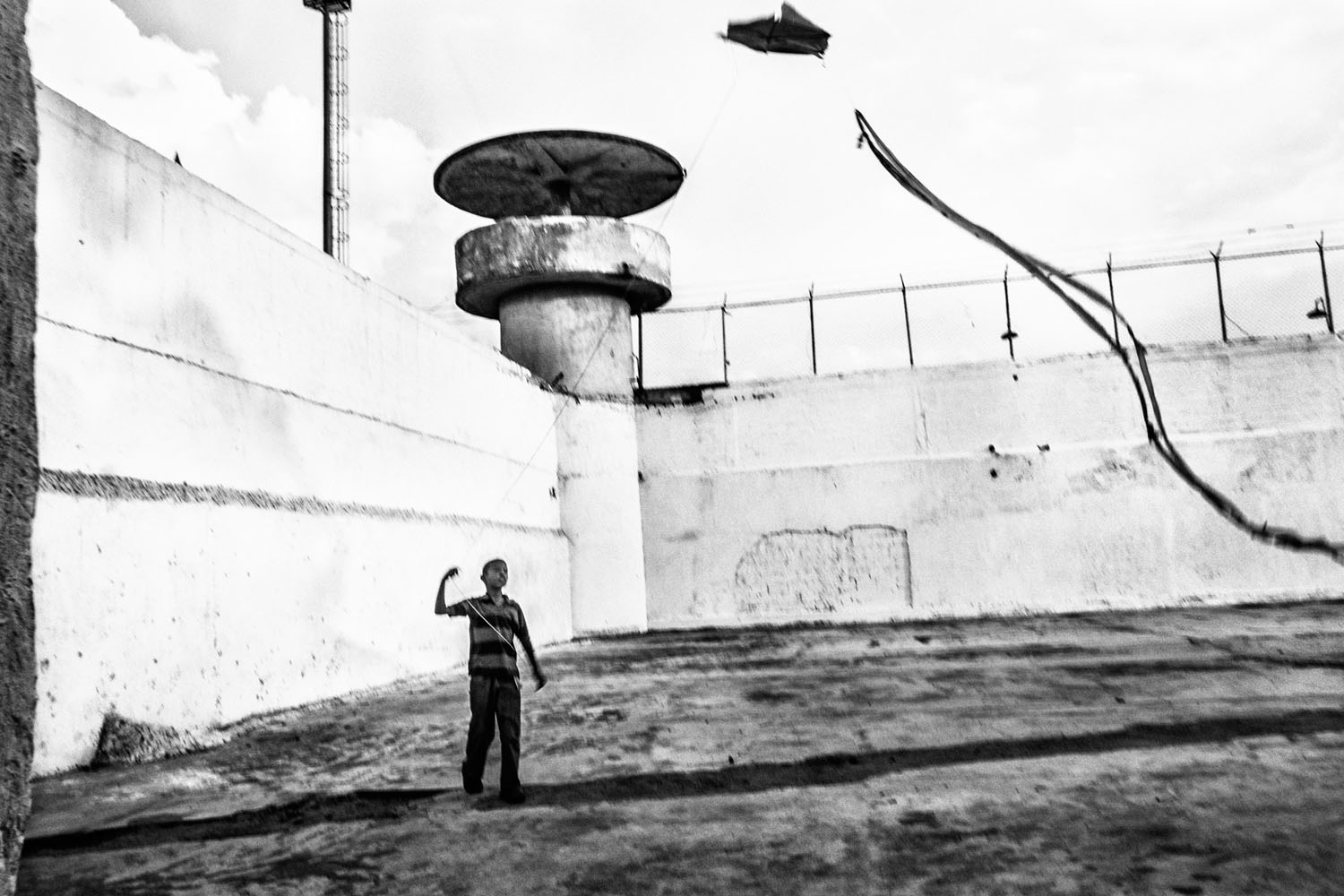 A child flies a kite in front of a security post of the Bolivarian National Guard, the official agency  responsible for ensuring the security of the Venezuelan prisons.