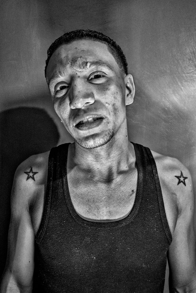 Portrait of an inmate with scars and tattoos from years in confinement.