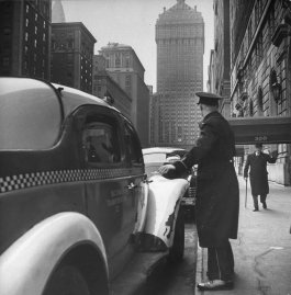 A New York City doorman flags down a taxi for one of the residents of his building, 1944.
