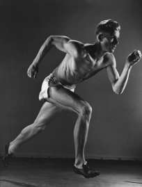 Runner photographed during an ICAAAA (Intercollegiate Association of Amateur Athletes of America) track meet, 1938.