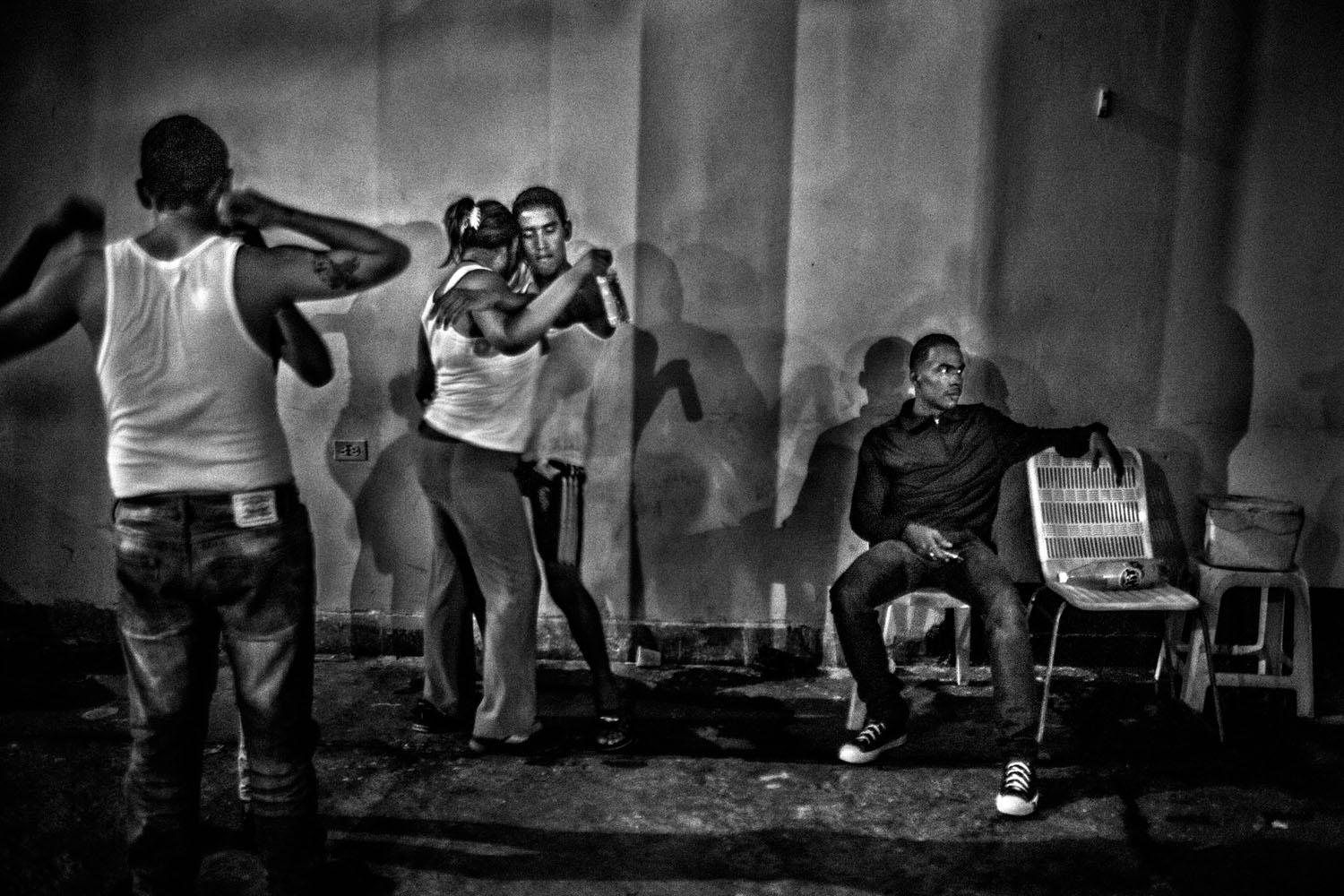 Inmates dance with girls during a weekend visit. In the background, an armed member of the carro keeps watch.