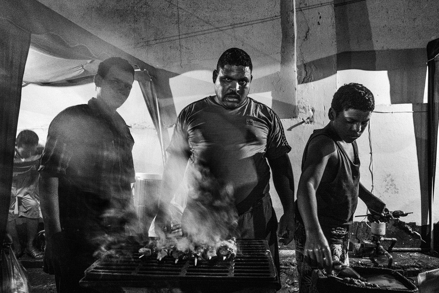 With his two sons, a prisoner grills meat to sell to other inmates and their visitors. Since the inmates have taken control of the prison, they have the freedom to run their our businesses.