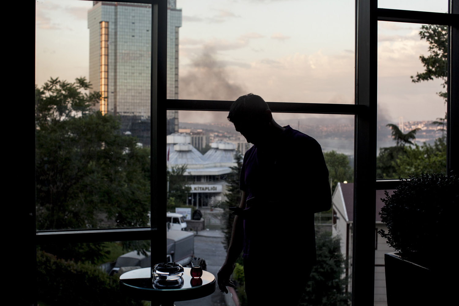 A man takes tea at a hotel balcony that overlooks Gezi park and the Bosphorus sea. The smoke below is from the fires lit by anti-government protesters in the Besiktas neighborhood of Istanbul.