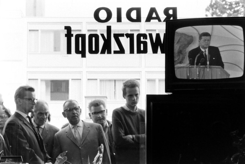 People watch and listen to John F. Kennedy on TV during his June 1963 visit to Germany.