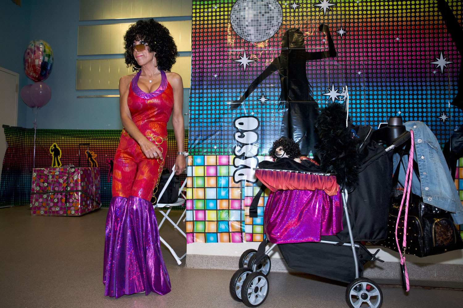 Teresa Costanza dancing at ZZ and Pebbles' disco themed birthday party while her Chihuahua, Yum Yum, watches.