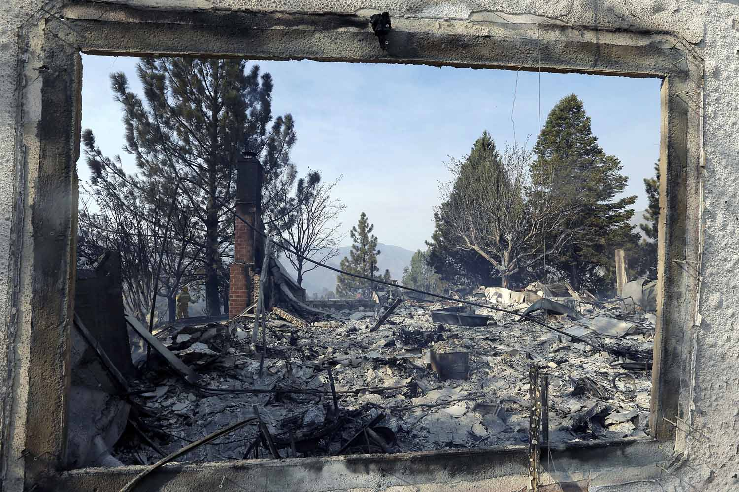 June 2, 2013. A window frames the view of a home damaged by wildfires in Lake Hughes, CA.