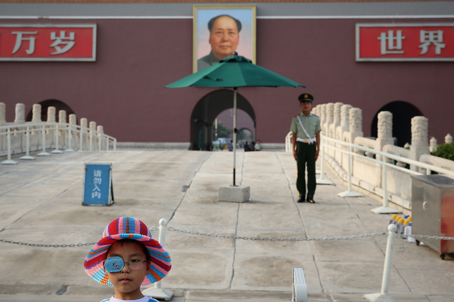 June 3, 2013. A little boy poses for photo as a Chinese paramilitary policeman guarding before the customary ceremony of lowering flag at Tienanmen Square in Beijing.