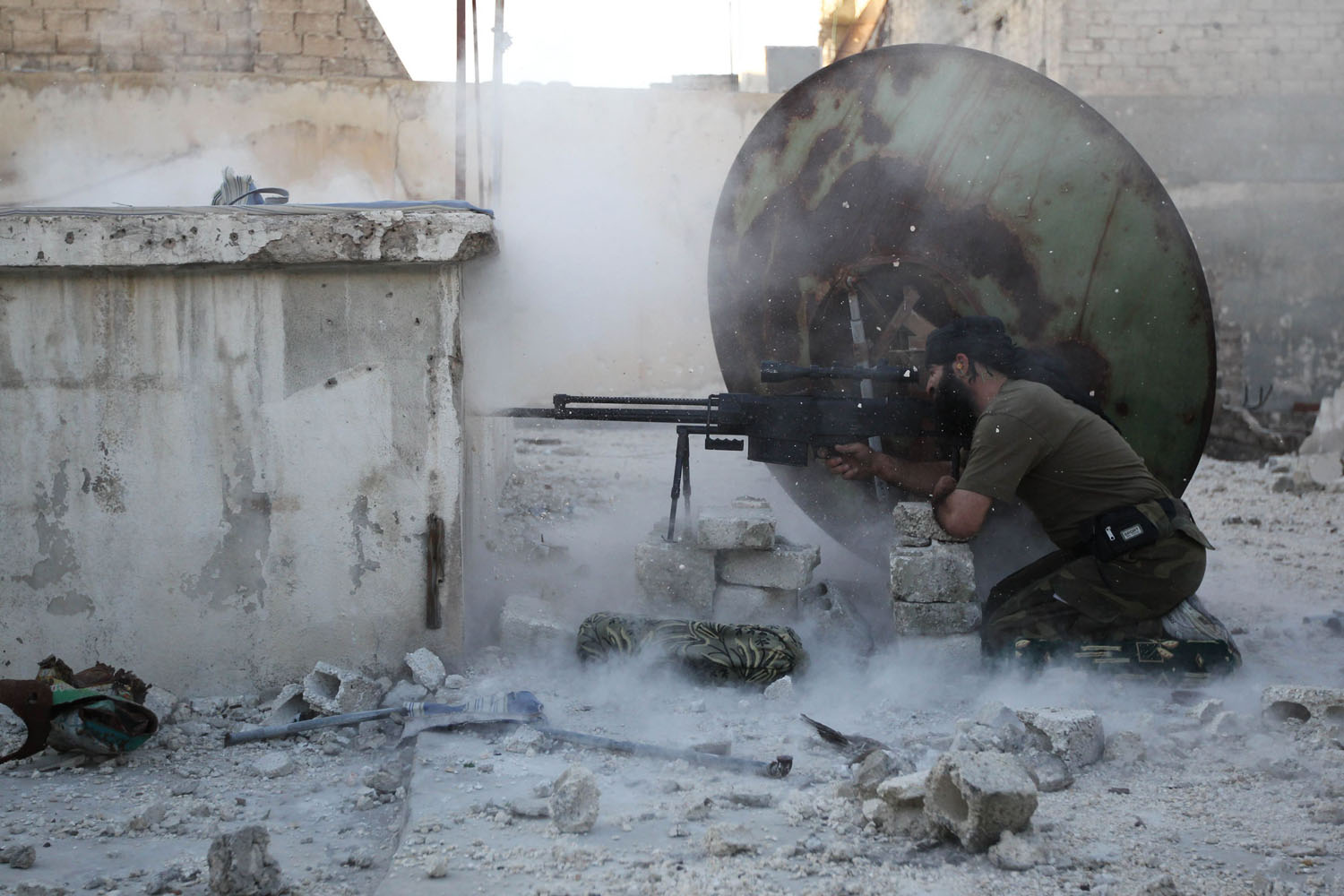 June 3, 2013. A member of the Free Syrian Army shoots back at a sniper during what activists said were clashes with pro-government forces in Aleppo's Karm al-Jabal district.