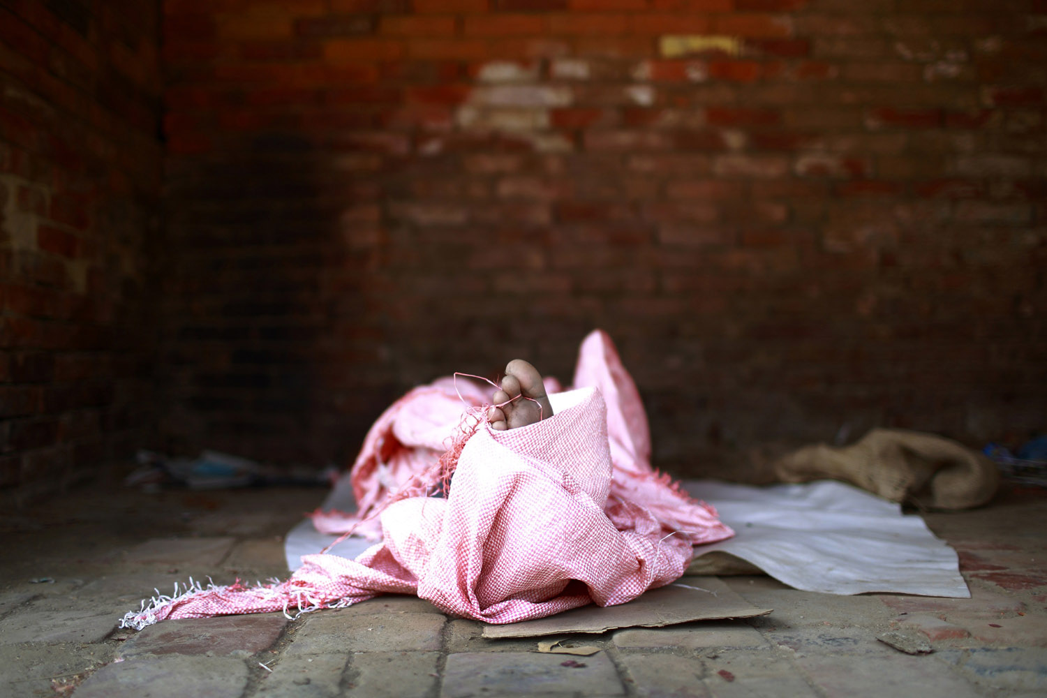 June 4, 2013. The toe of a street child pokes out from a sack as he sleeps along the streets of Lalitpur, Nepal.
