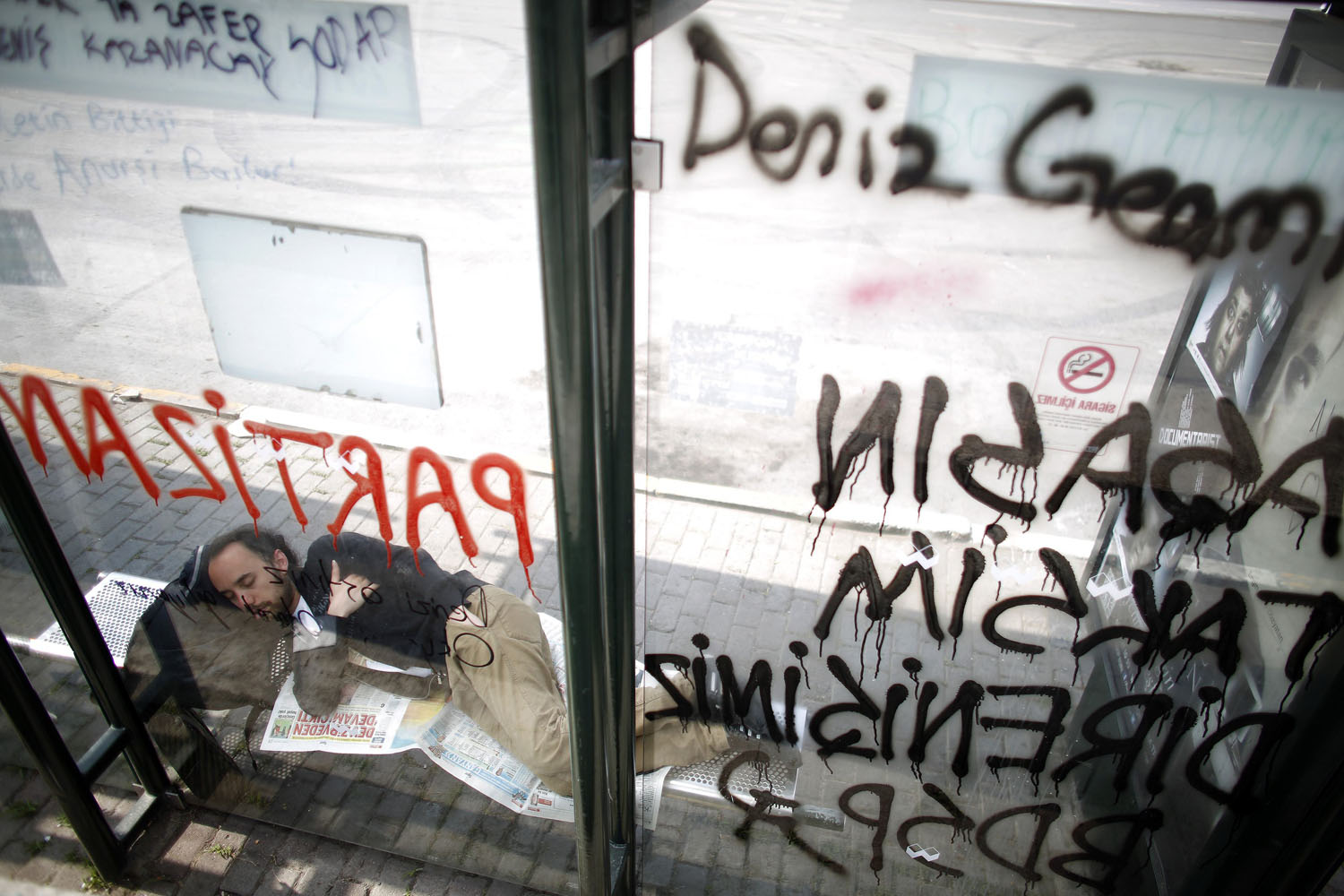 June 4, 2013. A protester sleeps at a bus stop sprayed with graffiti at Taksim Square in Istanbul, Turkey.