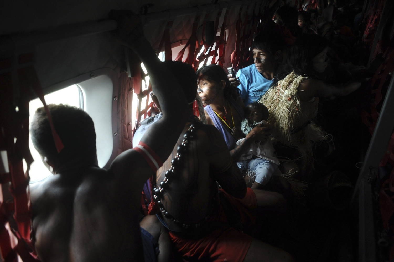 June 4, 2013. Munduruku Indians, many of who are flying for the first time, look out the window of a Brazilian Air Force plane as they are transported them to Brasilia for talks with the government.