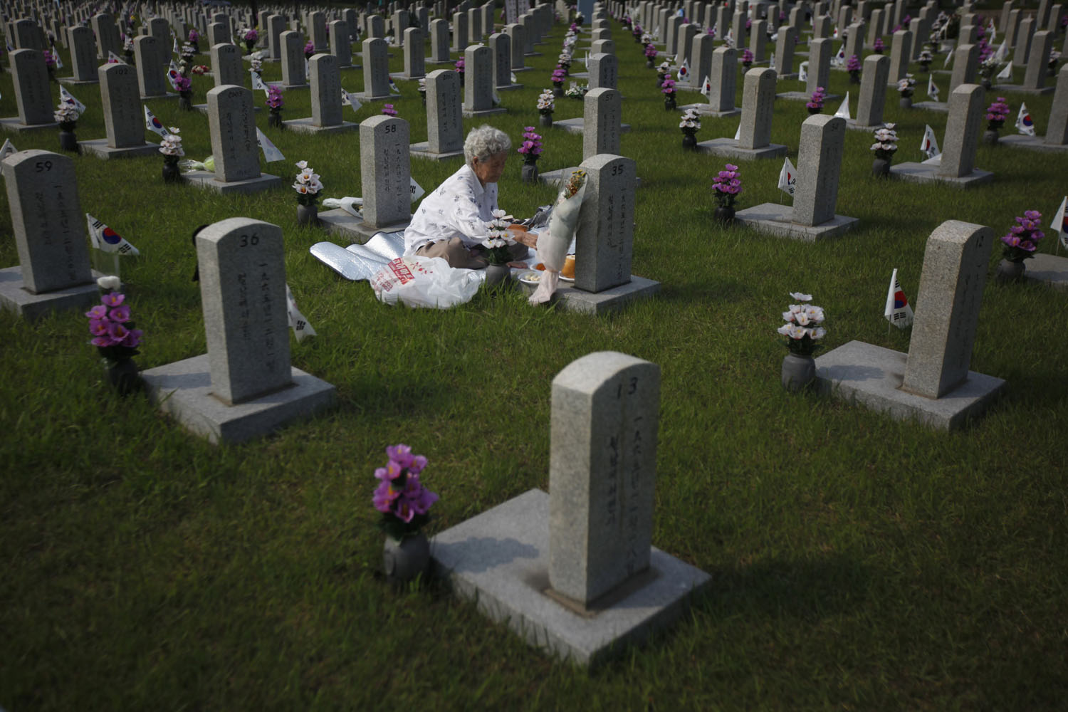 June 5, 2013. A woman pays her respects in front of the gravestone of her son who died for the country, at the national cemetery in Seoul, on the eve of South Korea's Memorial Day to commemorate fallen patriots.