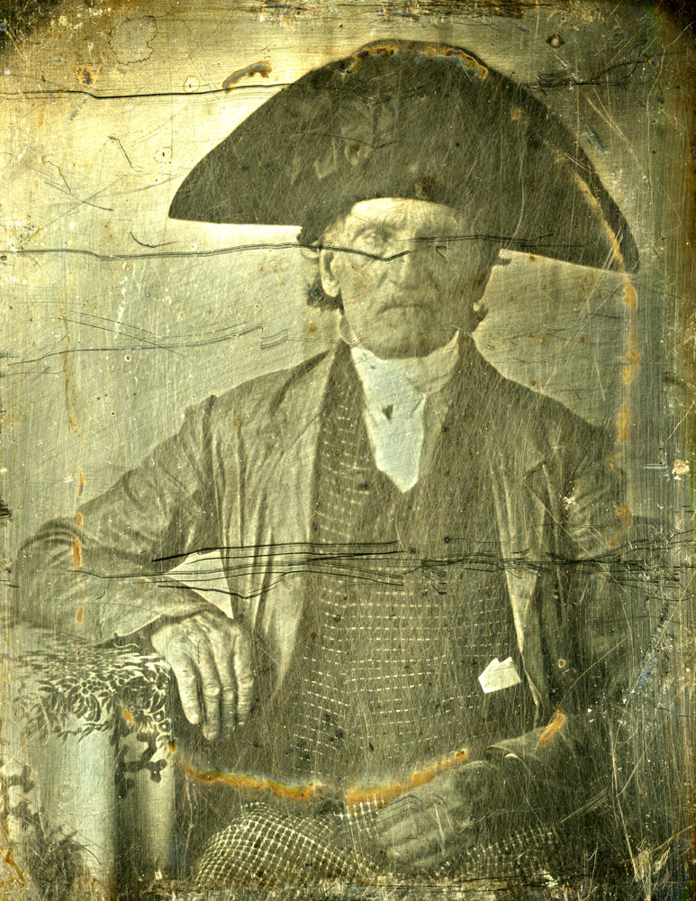 """George Fishley, daguerreotype.                                                              George Fishley was a soldier in the Continental army. When the British army evacuated Philadelphia and raced toward New York City, his unit participated in the Battle of Monmouth. Later he was part the genocidal attack on Indians who had sided with the British, a march led by General John Sullivan through """"Indian country,"""" parts of New York and Pennsylvania. Fishley's regiment, the Third New Hampshire, was in the midst of the campaign's only contested battle. After the Battle of Chemung, August 28, 1779, the Americans had devastated forty Indian towns and burned their crops. Later Fishley served on a privateer — a private ship licensed to prey on enemy shipping — and was captured by the British. Fishley was a famous character after the war in Portsmouth, New Hampshire, where he lived. He was known as """"the last of our cocked hats"""" — Continental soldiers wore tall, wide, Napoleonic-looking headgear with cockades. He marched in parades wearing the hat, which his obituary said """"almost vied in years with the wearer."""" Fishley is wearing the hat in the daguerreotype."""