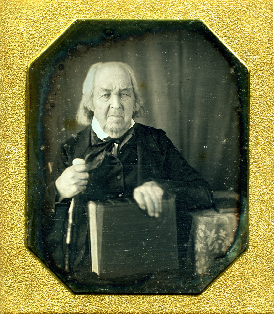 """Rev. Levi Hayes, daguerreotype.                                                              Rev. Levi Hayes was a fifer in a Connecticut regiment that raced toward West Point to protect it from an impending attack. He also participated in a skirmish with enemy """"Cow Boys"""" at the border of a lawless region called the Neutral Ground (most of Westchester County, New York, and the southwestern corner of Connecticut). In the early years of the nineteenth century, he helped organize a religiously-oriented land company that headed into the wilderness of what was then the West. They settled Granville, Ohio, where he was the township treasurer and a deacon of his church. His daguerreotype shows him holding a large book, most likely a Bible."""