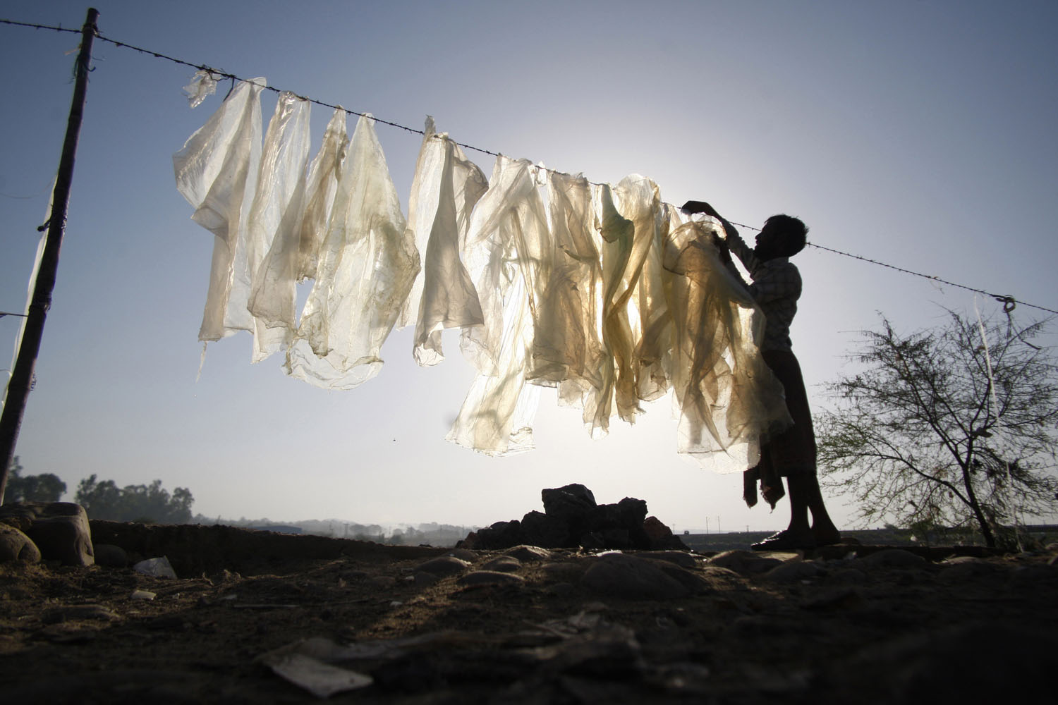 June 5, 2013. An Indian man dries plastic bags for reuse at an industrial area on the outskirts of Jammu, India.