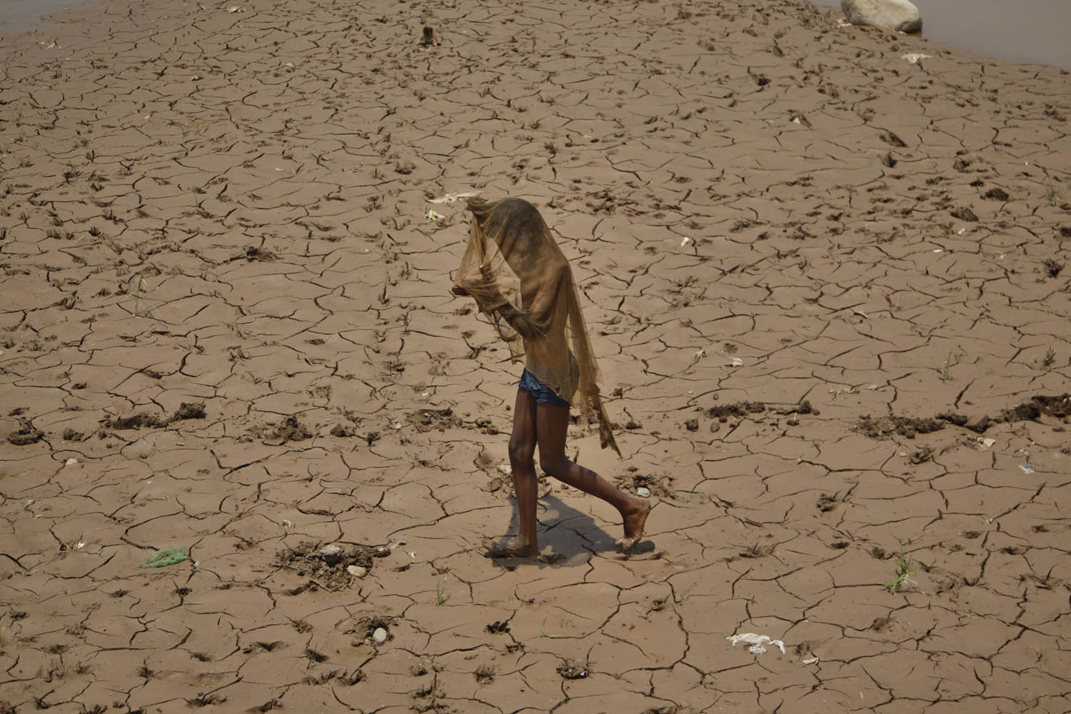 June 1, 2013. A young Indian covers his face to protect himself from the heat as he walks on a dried bed of the River Tawi on a hot summer day in Jammu, India.
