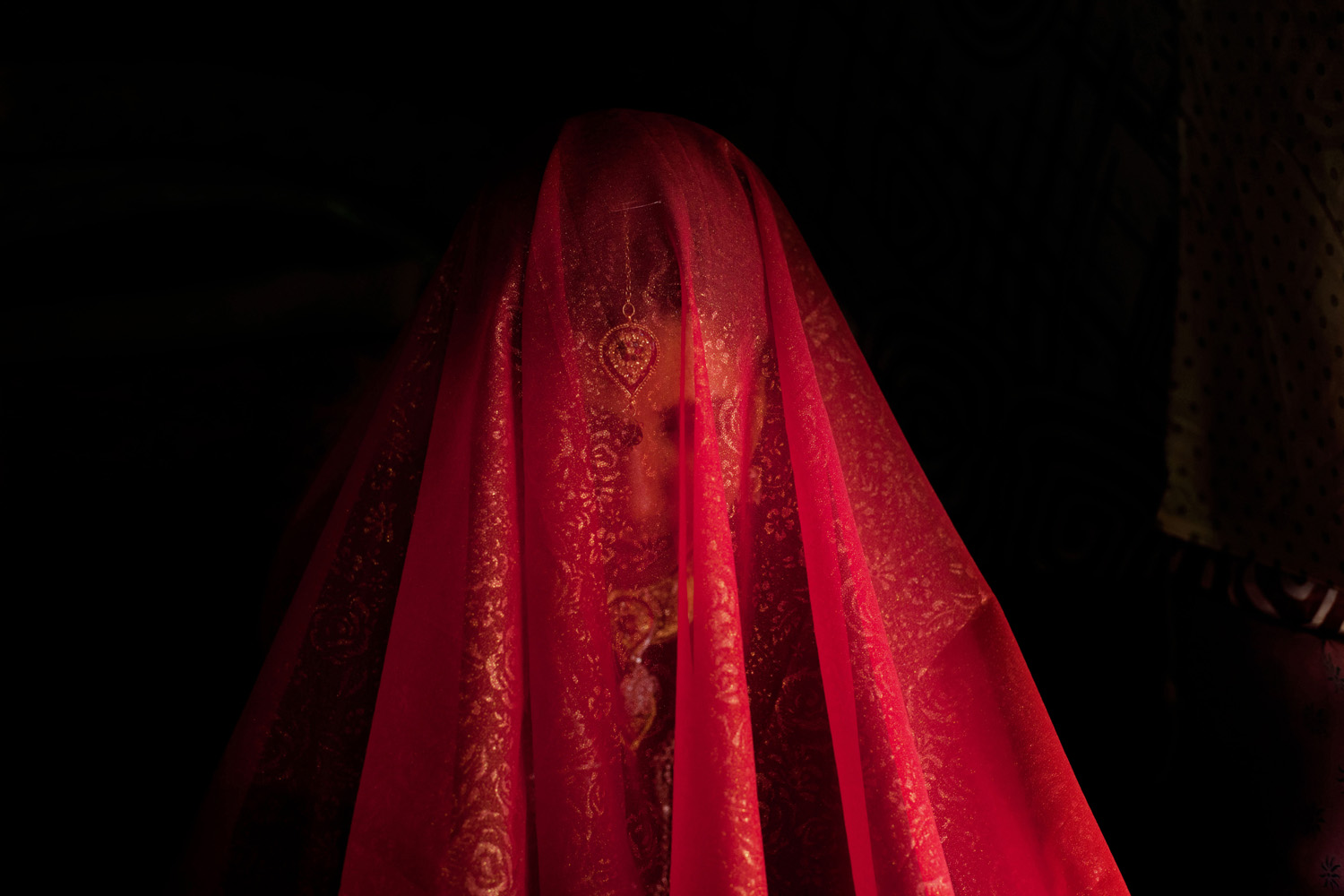 May 31, 2013. Zareena, a Kashmiri Bakarwal bride sits inside a temporary camp with her face covered with scarf during her wedding ceremony on the outskirts of Srinagar, India.