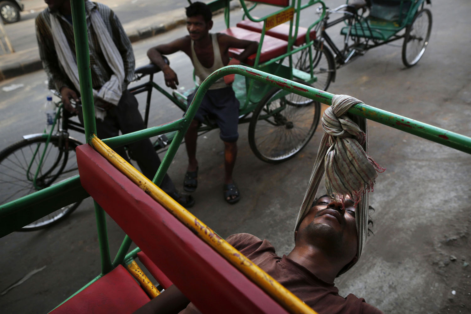 June 6, 2013. An Indian bicycle rickshaw walla uses a scarf to rest his head while sleeping on his rickshaw in New Delhi.