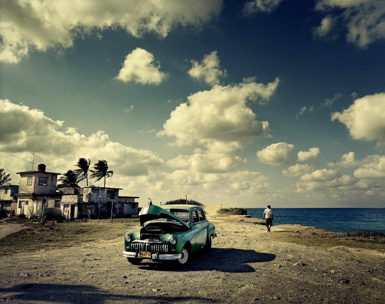An old American car, long a staple of Cuban roads, sits along Guanabo Beach, near Havana.