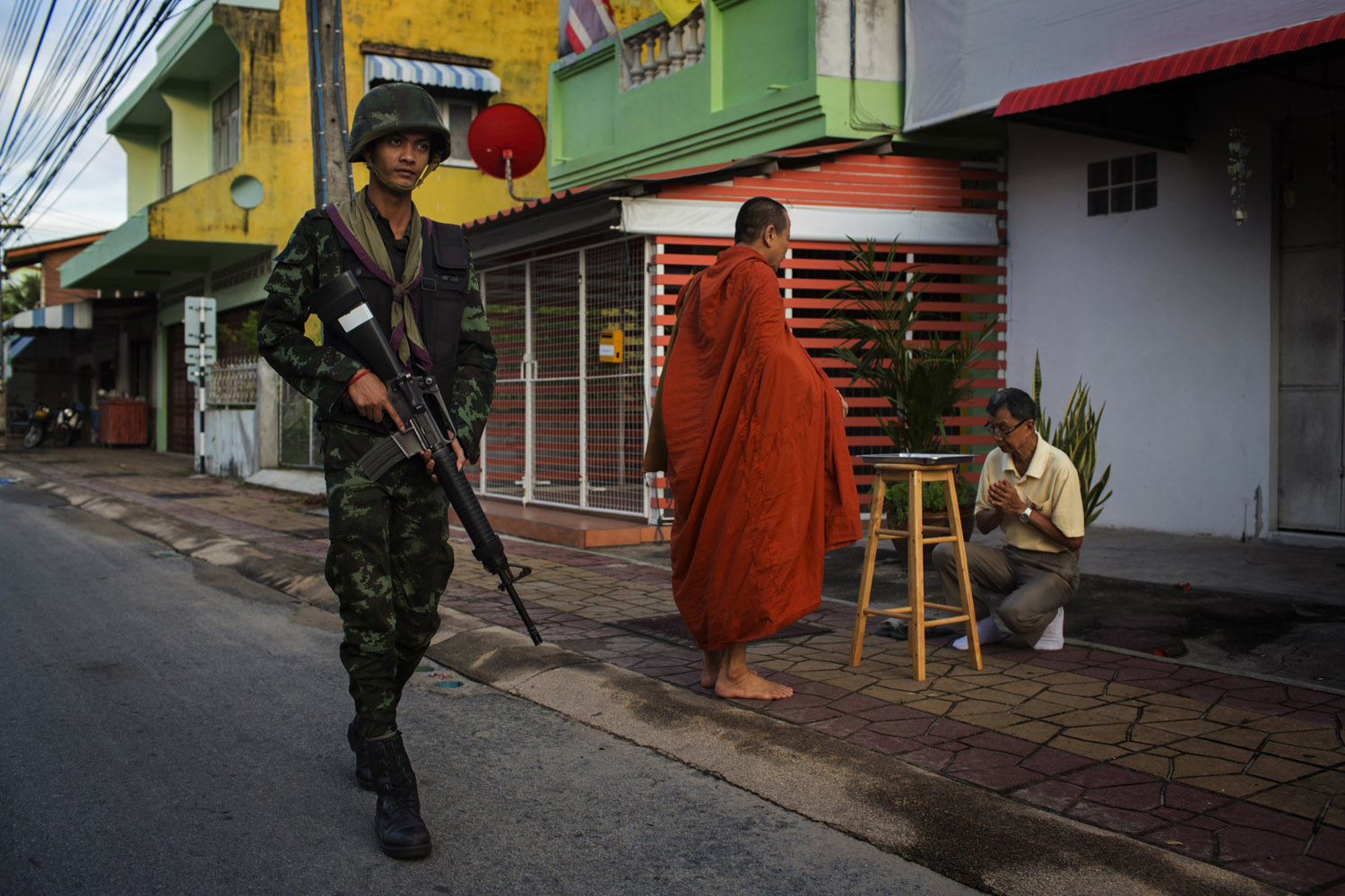 A Thai Army soldier provides security as monks from the Nopawong Saram Temple collect alms on their morning rounds in Pattani, Southern Thailand.