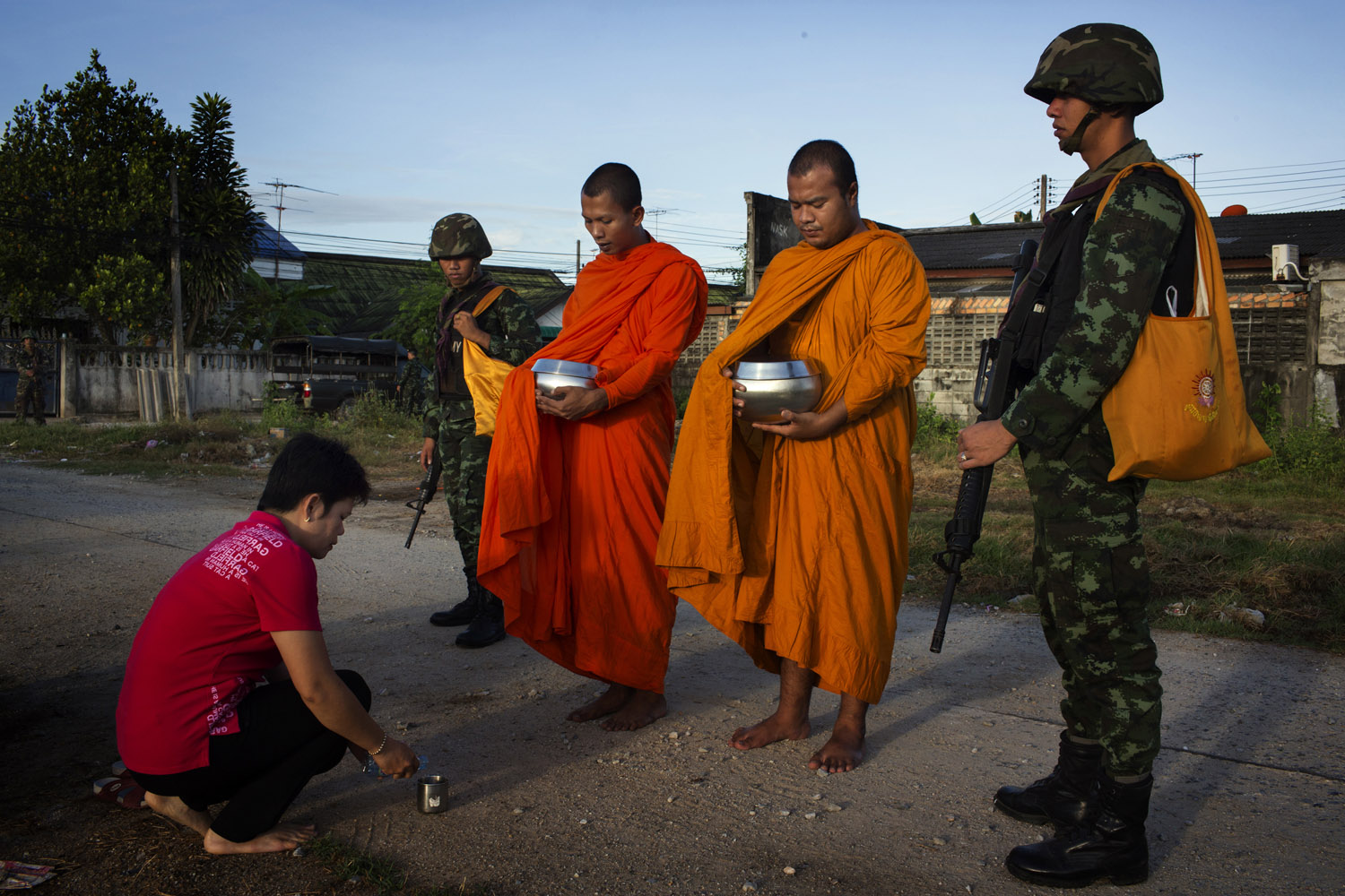 Soldiers from the 23rd Battalion of the Thai Army provide security as monks from the Lak Muang Temple collect alms in  Pattani.