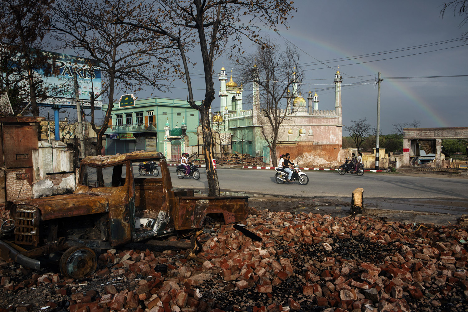 People drive past a burnt-out vehicle and damaged buildings, including a mosque, in the Mingalar Zayyone Muslim quarter, which was razed by Buddhists in ethnic violence in March, in Meikhtila, Burma.