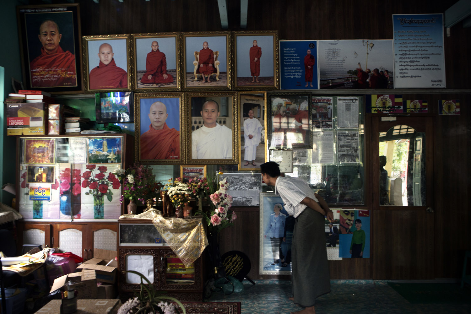 A supporters of Wirathu looks at photos of him on the wall of his quarters at the New Maesoeyin Monastery.