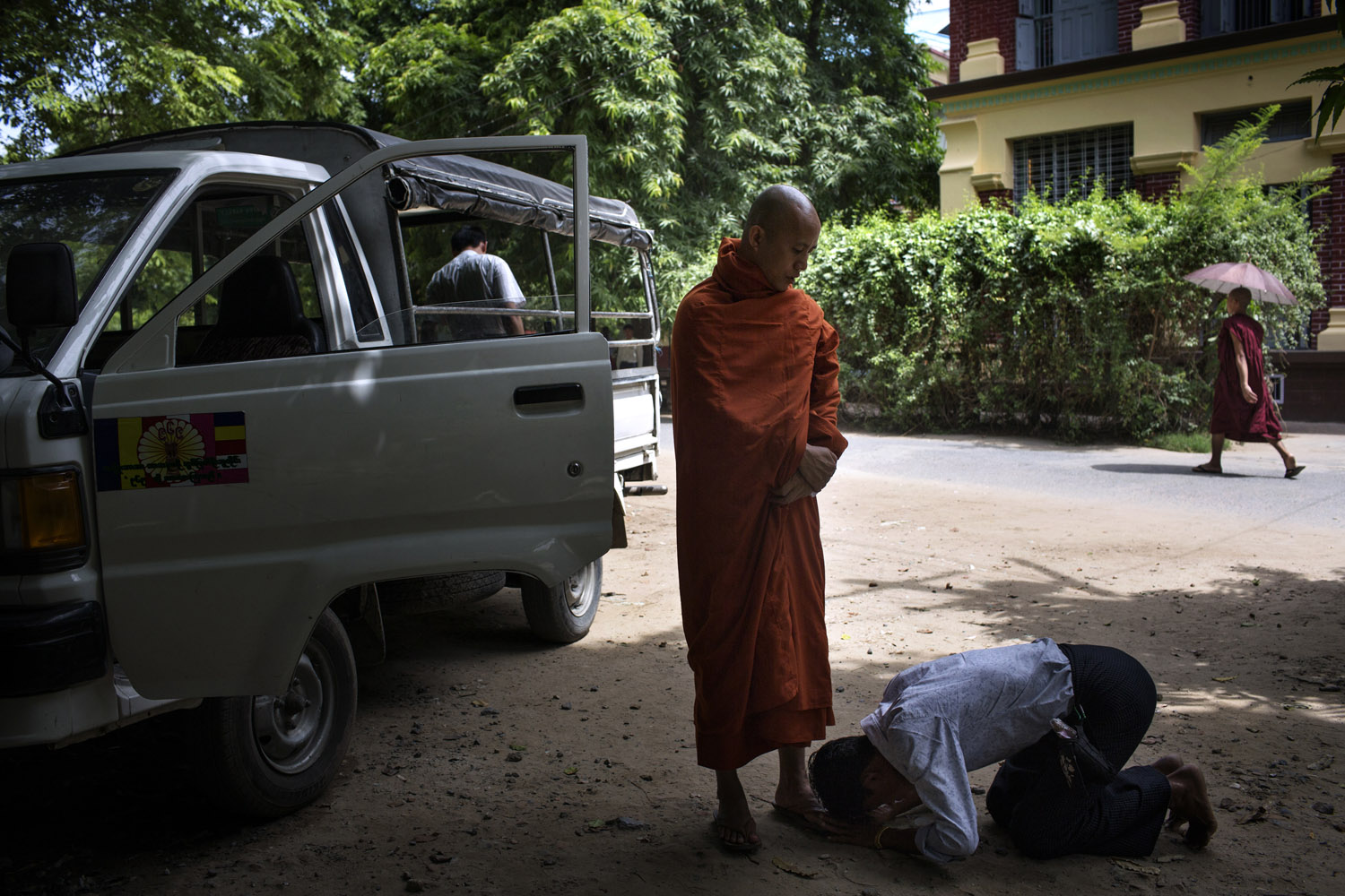 A Wirathu supporter bows at his feet outside his quarters at the New Maesoeyin Monastery in Mandalay.