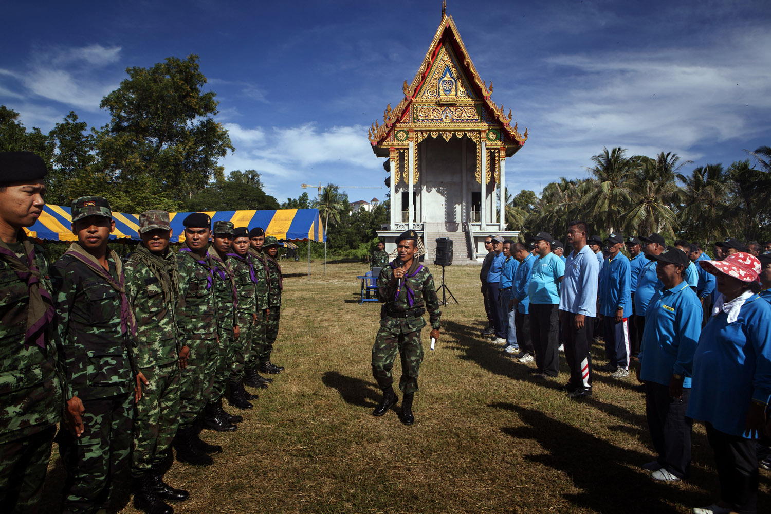 Lieutenant Sawai Kongsit (center) talks to military trainers from the 23rd Battalion of the Thai Army (left) and Buddhist volunteer defense militia (right) during a training session at the Lak Muang Temple in Pattani.