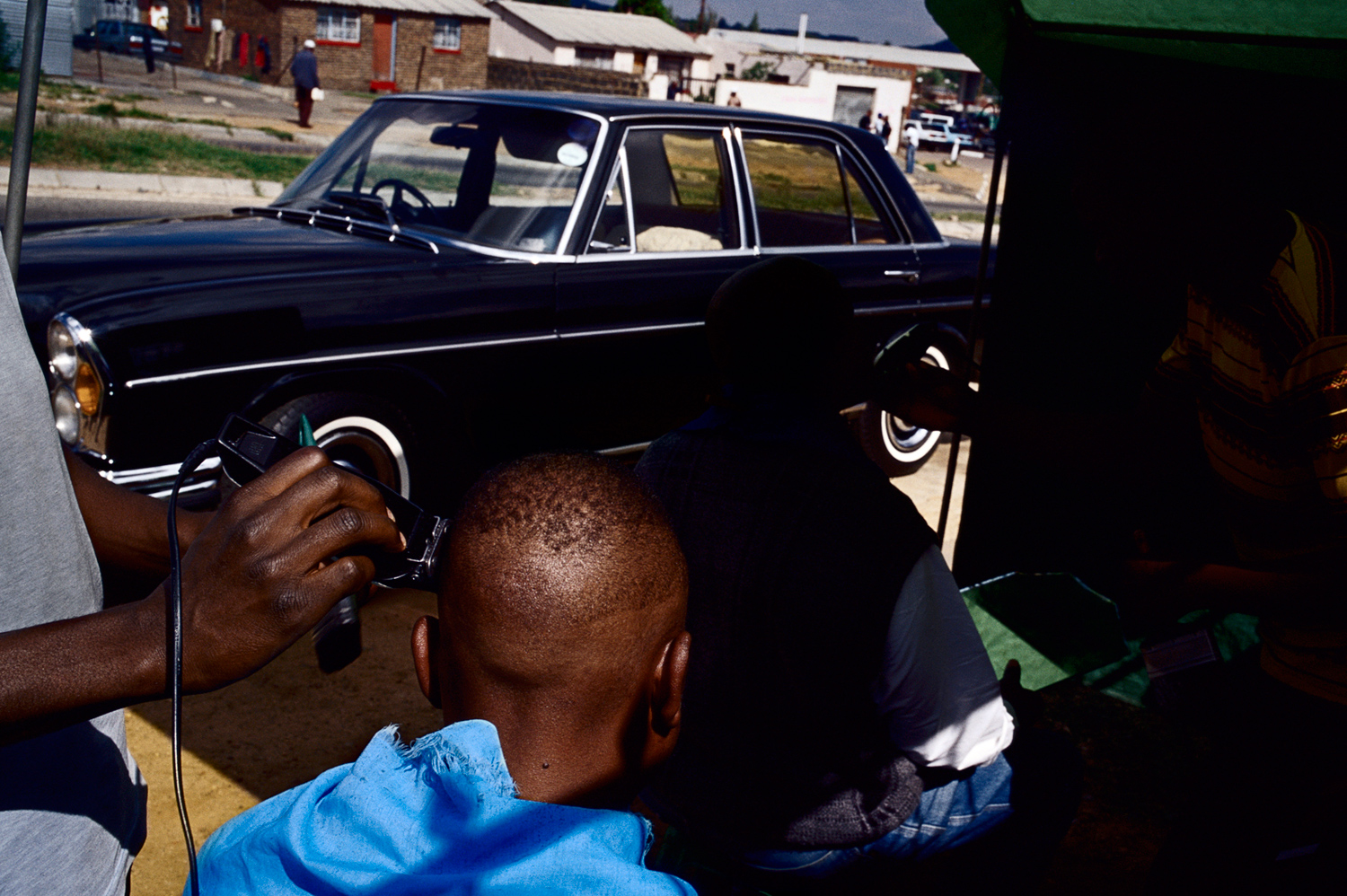 Barbershop haircut on a road in Diepkloof, Soweto, South Africa, March 2005.