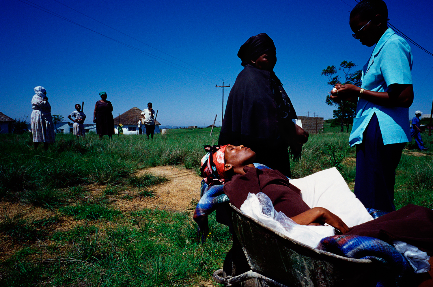 Busisiwe Mfeka, 28, is dying of Aids. She rests in a wheelbarrow, as a hospice worker drops off her and her mother in Izingolweni, a rural village in Southern Natal, South Africa, November 2005. South Africa has one of the highest HIV/Aids infection rates worldwide and also the largest ARV drugs programme.